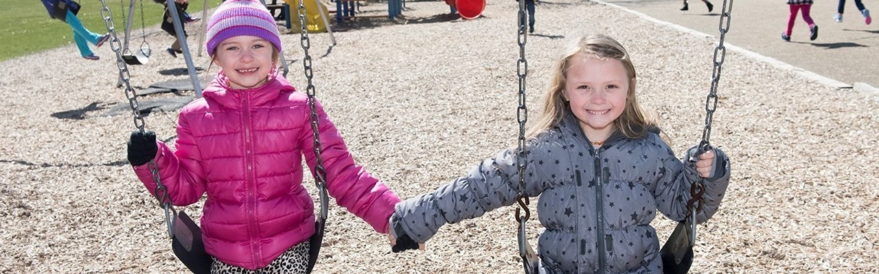 two girls on swings holding hands