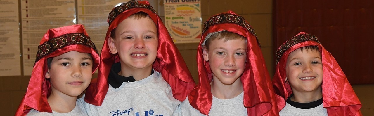 "Four boys dressed for performance of ""Aladdin"""
