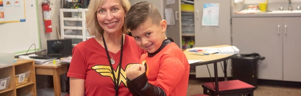 Blonde teacher in Wonder Woman shirt with little boy dressed as a super hero