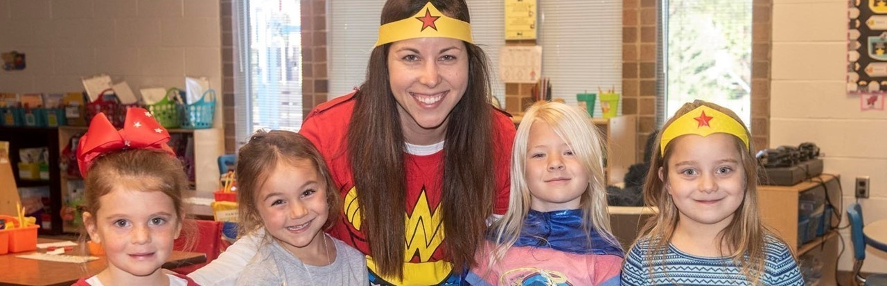 teacher with four girls dressed as Wonder Woman