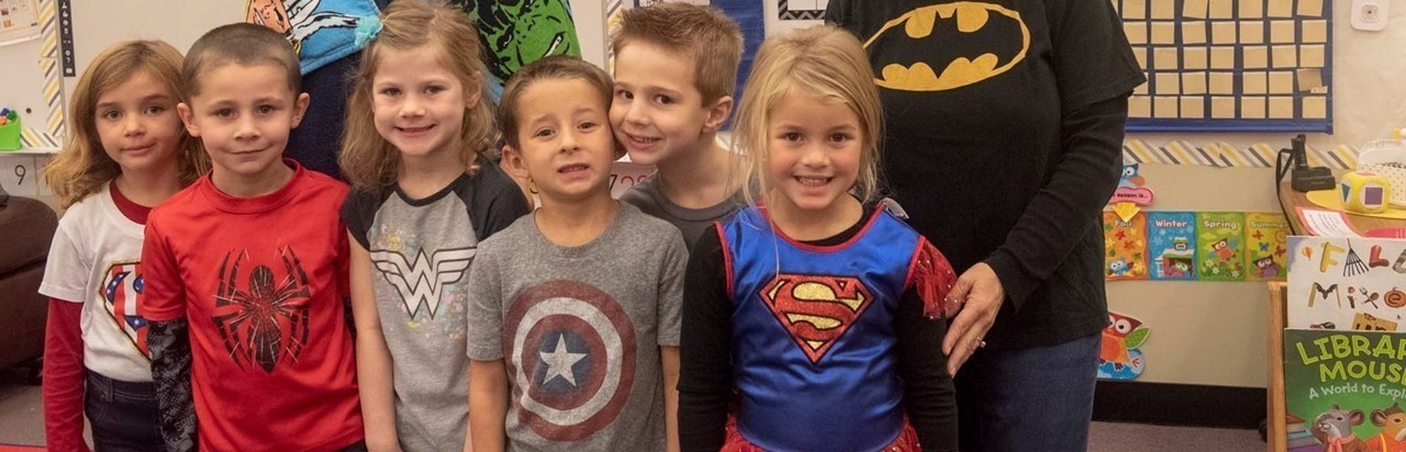 Two teachers and six students dressed as super heroes