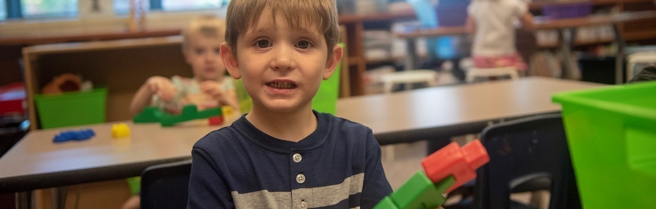 Preschool boy in a blue shirt playing with interlocking blocks