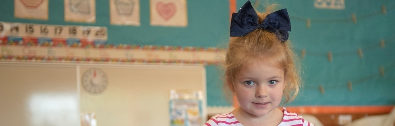 Preschool girl wearing a large blue bow in her hair