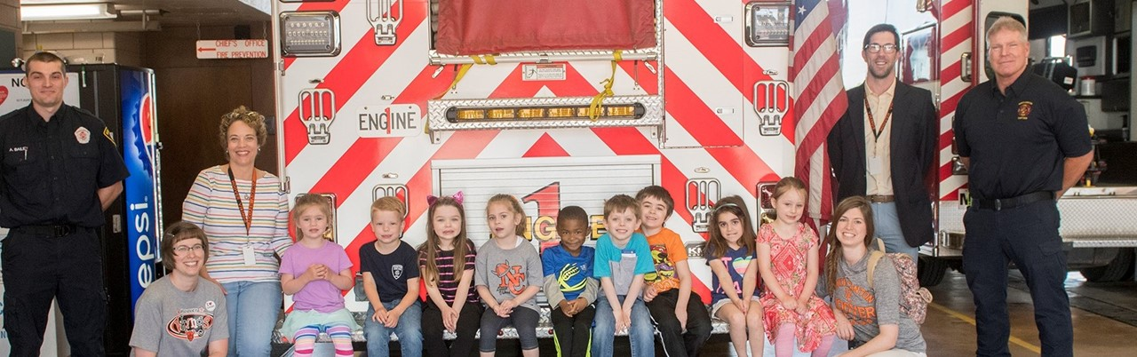 preschool students sitting on the bumper of a fire truck