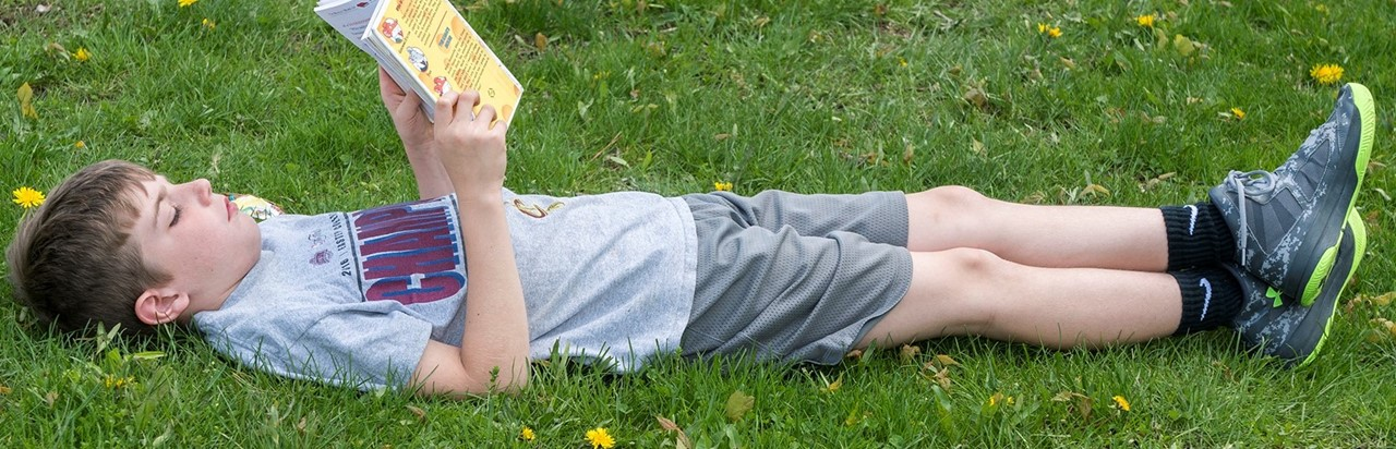 little boy reading a book outside in the grass