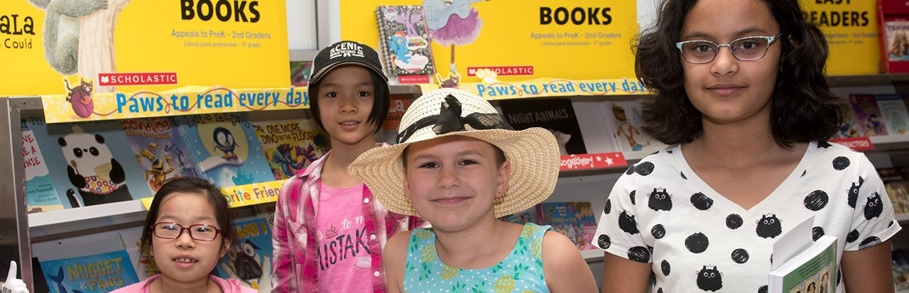 four children at the book fair in the intermediate school library