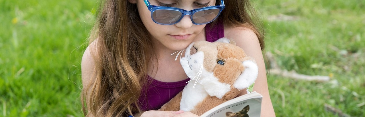 little girl reading a book while holding a stuffed animal