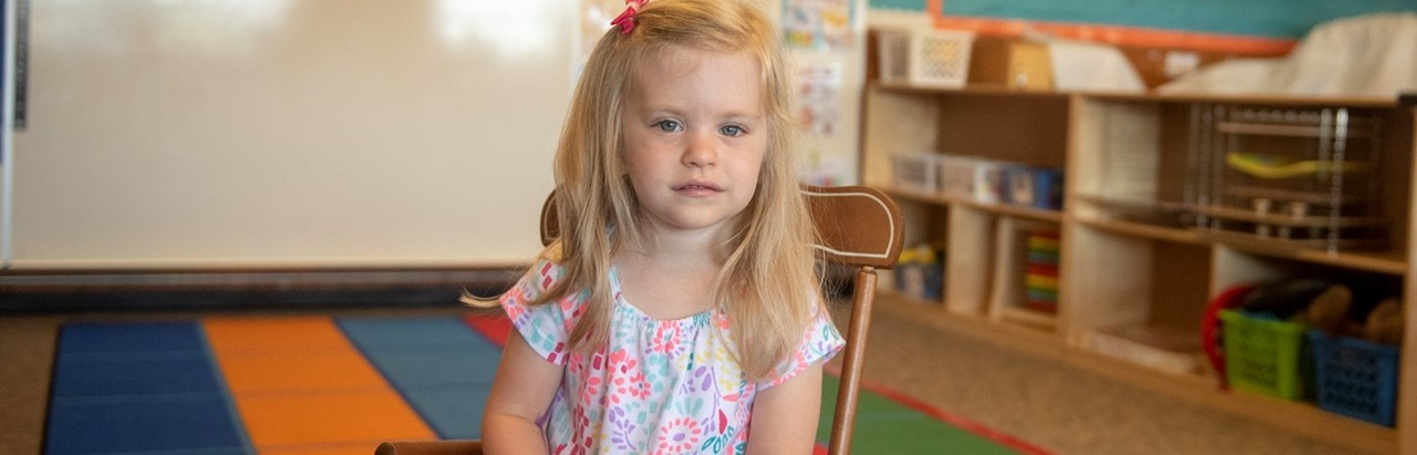 Blonde preschool student in a small rocking chair