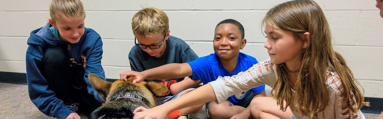 three boys and one girl petting a German Shepherd
