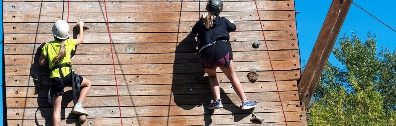 two middle school girls climbing wall