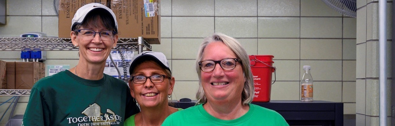 three lunch ladies wearing green