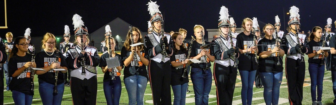 Eighth-grade students playing with high school marching band