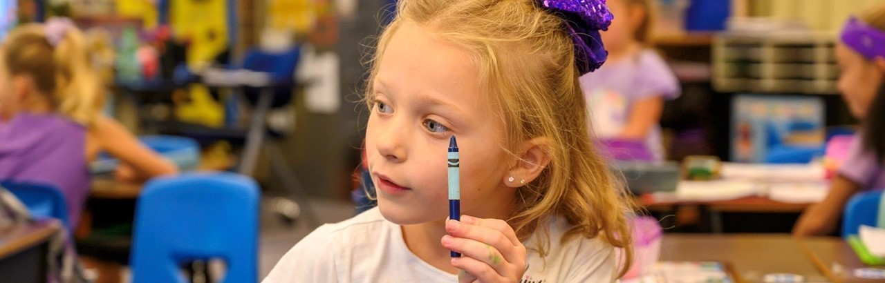 little girl with a purple ribbon in her hair holding a crayon