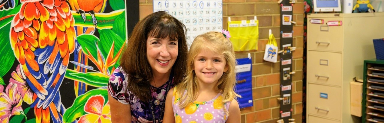 brown-haired teacher with blonde student in a purple dress