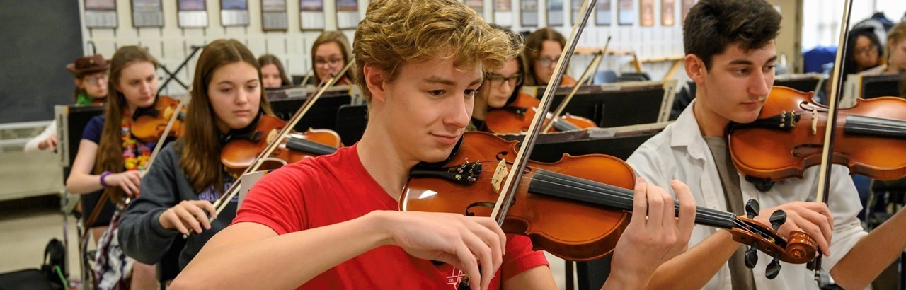 high school students playing the violin