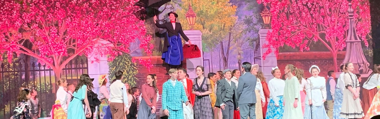 Mary Poppins flying above the townshpeople