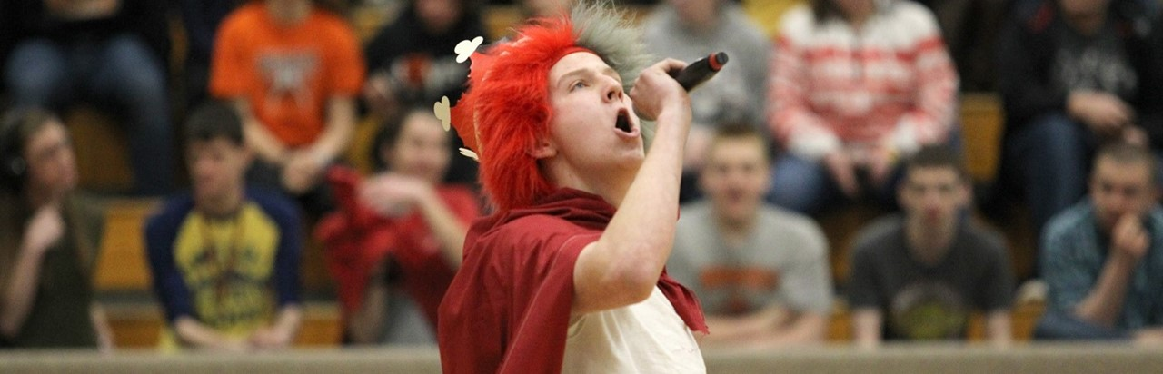 male student with an orange wig and red cape holding a microphone