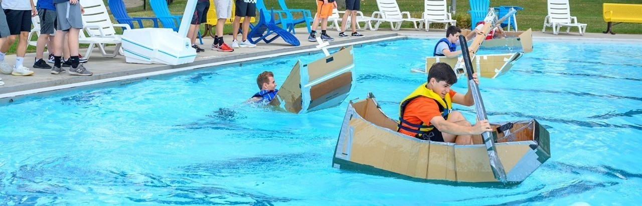 senior boys competing in a cardboard boat challenge
