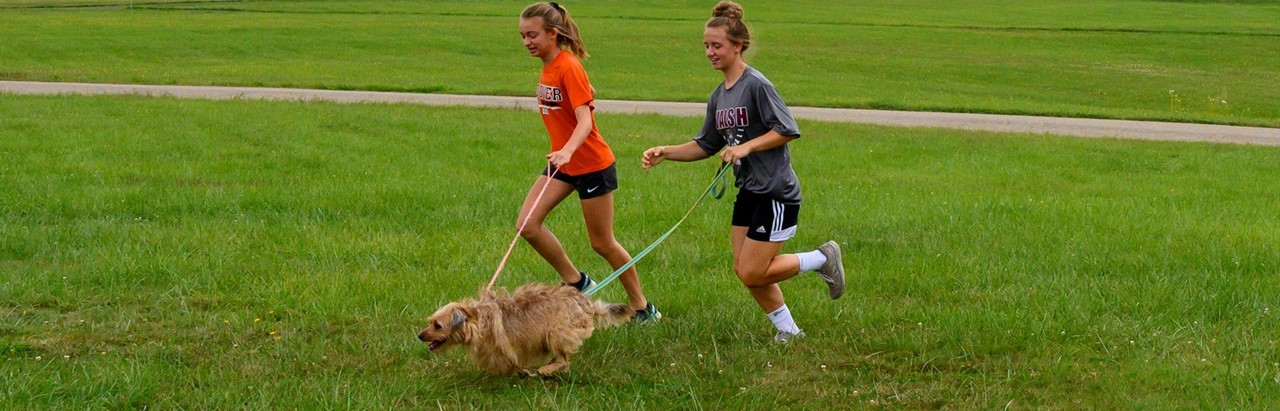two middle school girls running with a dog
