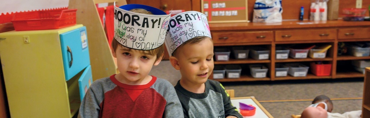 two little boys wearing crowns for their first day of preschool