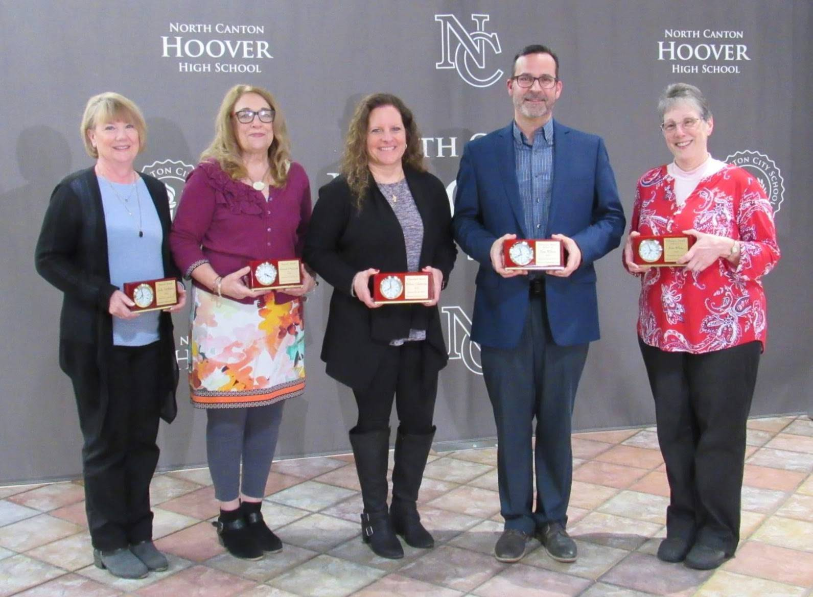 Four women and one man holding awards