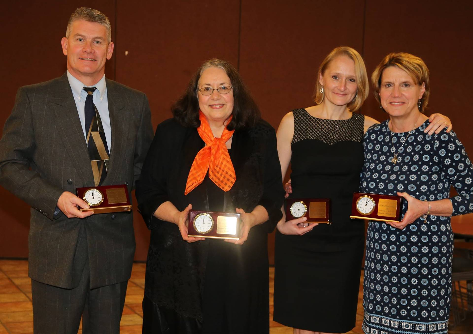 One man and three women holding awards