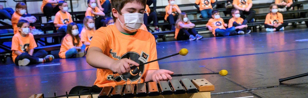 little boy with brown hair and orange shirt playing the xylophone
