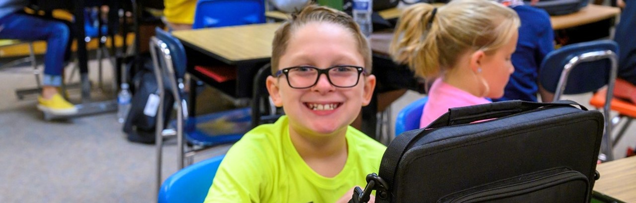 little boy wearing glasses and a green shirt